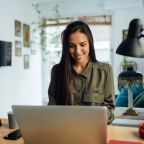 Happy attractive young woman of middle eastern ethnicity, working from home, using a laptop